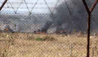 Plumes of smoke rise from burning tires during a plane-crash drill at Harare International Airport in Zimbabwe on Aug. 5. The mock exercise created panic. (Associated Press)