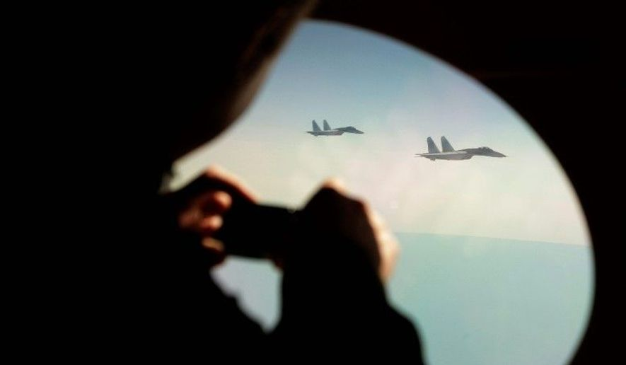 FILE: A colonel in the Canadian Forces takes photos through the window of a civilian aircraft playing the role of a hijacked airliner as it is escorted by two Su-27 Russian fighter jets. (Associated Press)
