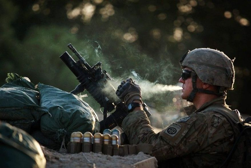 U.S. Army Spc. Nicholas Fischer smokes as he stands guard in the Arghandab Valley of Afghanistan. A law, meant to deter smuggling and underage sales of tobacco through the mail, has blocked family and friends from shipping packages containing cigarettes to troops. (Associated Press)