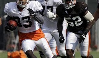 Cleveland Browns linebacker D'Qwell Jackson (52) chases wide receiver Chansi Stuckey during an NFL football training camp practice Tuesday morning, Aug. 10, 2010, in Berea, Ohio. Jackson, who spent most of the 2009 season on injured reserve with a torn right pectoral muscle, injured his left pectoral at the Tuesday evening practice. (AP Photo/Mark Duncan)
