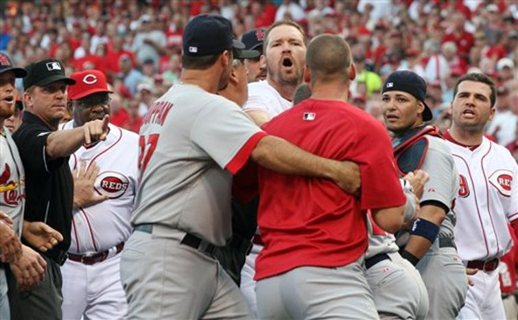 Cincinnati Reds Scott Rolen forth from right, yells at an unidentified St. Louis Cardinals player being held back by teammate Jeff Suppan while umpire Mark Wegner holds back Cincinnati Reds manager Dusty Baker, right, during an altercation in the first inning of their baseball game in Cincinnati Tuesday Aug. 10, 2010. Cardinals catcher Yadier Molina and Reds Joey Votto, far right, listen. (AP Photo/Tom Uhlman)