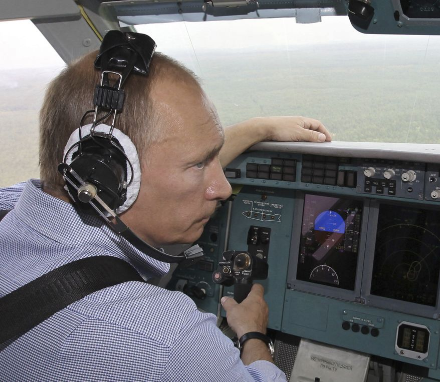 Russian Prime Minister Vladimir Putin sits in the cockpit of an Emergency Ministry Beriev Be-200 amphibian multirole jet flying a water drop over forest fires in Russia's Ryazan region, some 111 miles southeast of Moscow, on Tuesday, Aug. 10, 2010. (AP Photo/RIA Novosti, Alexei Nikolsky, Pool)