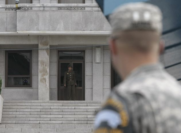 A North Korean soldier, left, looks at the southern side as an U.S. Army soldier looks on at the border village of Panmunjom, South Korea, on Wednesday, Aug. 11, 2010. Relations between the two Koreas have been tense since the deadly sinking of a South Korean warship in late March that Seoul and the United States blame on North Korea. (AP Photo/Ahn Young-joon)