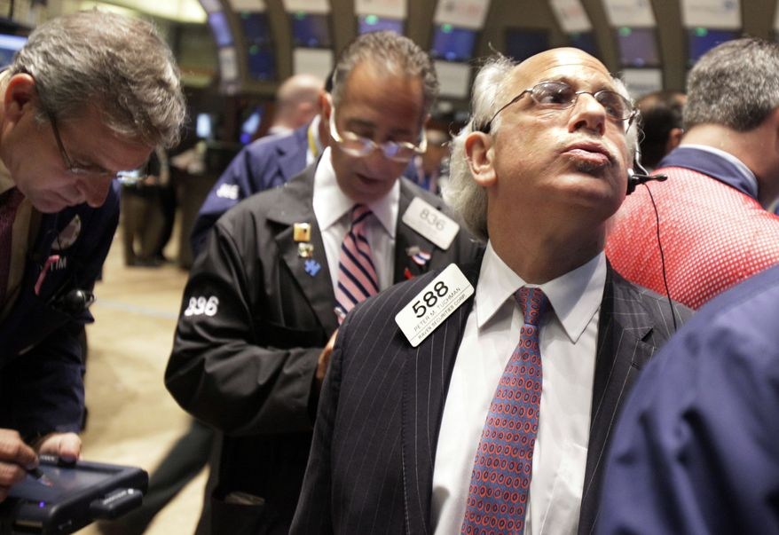 Trader Peter Tuchman (right) watches the numbers as he works on the floor of the New York Stock Exchange on Tuesday, Aug. 10, 2010. (AP Photo/Richard Drew)