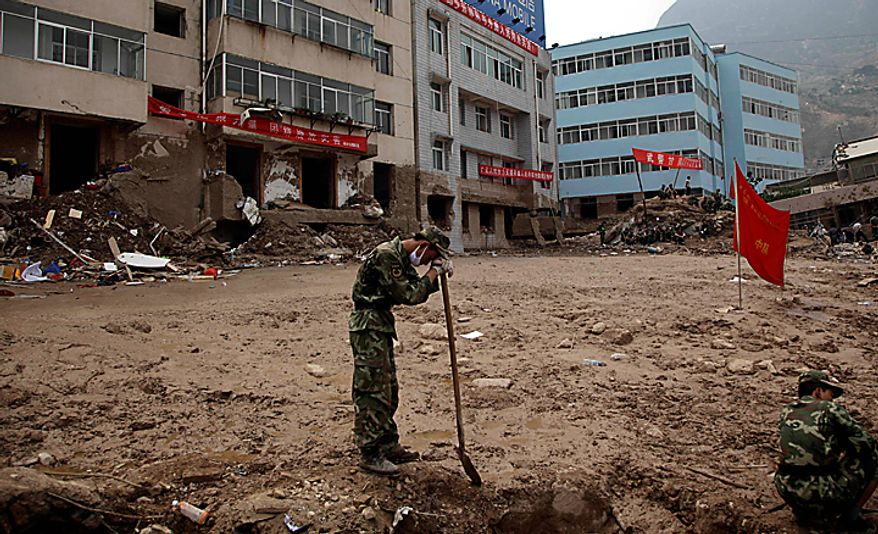A Chinese soldier rests on his shovel during an effort to dig out victims a mud slide that swept into the town of Zhouqu in Gannan prefecture of northwestern China's Gansu province, Wednesday, Aug. 11, 2010. (AP Photo/Ng Han Guan)
