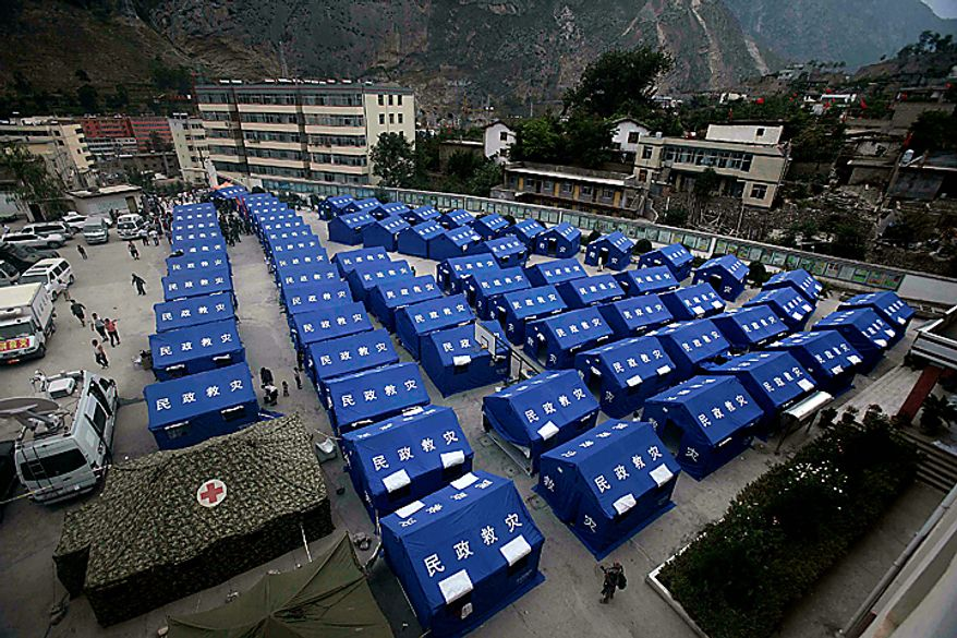 In this photo taken Tuesday, Aug. 10, 2010, released by China's Xinhua News Agency, people walk among disaster relief tents set up at the No.3 Middle School in Zhouqu County, Gannan Tibetan Autonomous Prefecture in northwest China's Gansu Province. Heavy rains Wednesday lashed the remote section of northwestern China where weekend flooding killed at least 702 people, as hopes of finding more survivors faded and crews worked to stave off outbreaks of disease. (AP Photo/Xinhua, Wang He)