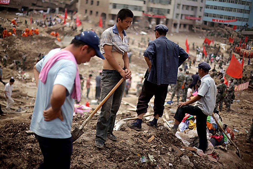 Residents rest from their effort to recover bodies after a mudslide swept into the town of Zhouqu in Gannan prefecture of northwestern China's Gansu province, Wednesday, Aug. 11, 2010.  Heavy rains Wednesday lashed a remote section of northwestern China as the death toll from weekend flooding that triggered massive landslides jumped to more than 1,000 and the hopes of finding more survivors faded. (AP Photo/Ng Han Guan)