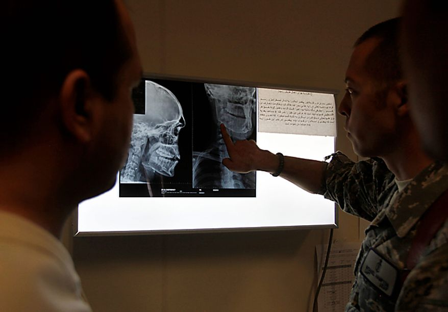 U.S Air Force Physician-Mentor Capt. Michael Hampton, right, of the Medical Training Advisory Group, or MTAG, stands with Afghan doctors discussing the x-ray of an Afghan soldier with a gunshot wound to the neck and face, at Kandahar Regional Military Hospital, KRMH, inside Camp Hero, Kandahar province, southern Afghanistan, Sunday, Aug. 8, 2010.  The MTAG team, comprised of 12 U.S. Air Force medical professionals, assigned to the Afghan military hospital, and are tasked with providing transitional guidance to local medical workers, who treat Afghan soldiers, civilians, and occasionally insurgents. (AP Photo/Brennan Linsley)