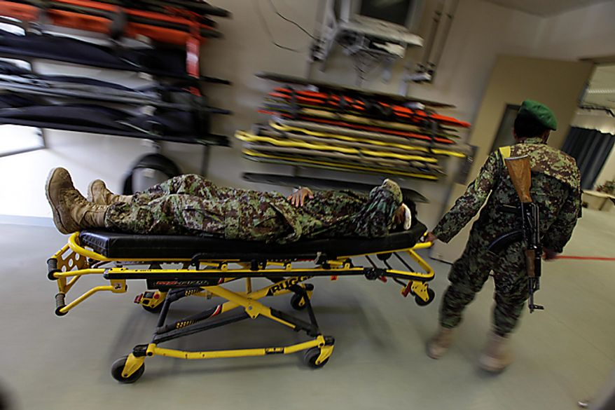 An Afghan army soldier wheels a wounded fellow soldier into the ER at Kandahar Regional Military Hospital, KRMH, inside Camp Hero, Kandahar province, southern Afghanistan, Saturday, Aug. 7, 2010.  A U.S Air Force Medical Training Advisory Group, or MTAG team, comprised of 12 medical professionals, is assigned to the Afghan military hospital, and are tasked with providing transitional guidance to local medical workers, who treat Afghan soldiers, civilians, and occasionally insurgents. (AP Photo/Brennan Linsley)