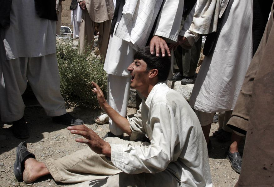 An Afghan mourns for relatives who other mourners say were killed by NATO forces during a raid in the Sayed Abad district of Wardak province west of Kabul, Afghanistan, on Thursday, Aug. 12, 2010. (AP Photo/Rahmatullah Naikzad)