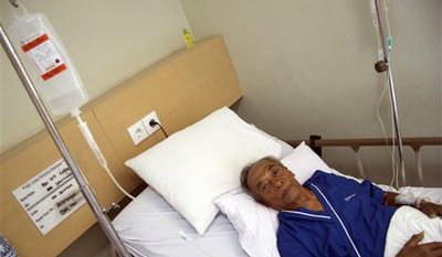 """The Balinese fortuneteller featured in Elizabeth Gilbert's best-selling memoir """"Eat Pray Love"""" Ketut Liyer lies on a hospital bed, accompanied by his grand daughter Ni Wayan Puspitasari in Denpasar, Bali, Indonesia, Thursday, Aug. 12, 2010. Liyer has been hospitalized because of a heart ailment _ just days before a movie adaptation starring Julia Roberts hits U.S. theaters, his doctor said Thursday. (AP Photo)"""
