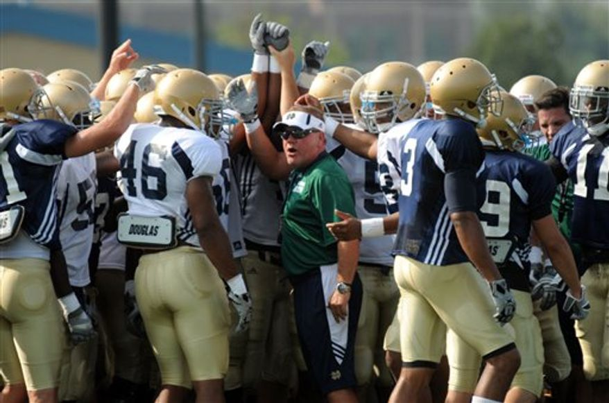 Notre Dame football coach Brian Kelly huddles with his team  during practice Wednesday Aug. 11, 2010,  in South Bend, Ind. Notre Dame opens their season against Purdue Sept. 4. (AP Photo/Joe Raymond)