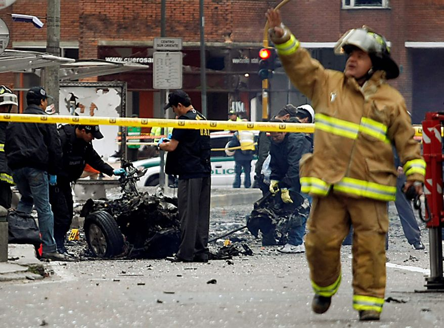 Agents from the police anti explosive unit, inspect the wreckage of a car bomb that exploded outside the building of Caracol Radio station in Bogota, Colombia, Thursday, Aug. 12, 2010. The explosion shook Colombia's capital on Thursday, injuring at least six people, police said. No deaths were reported. (AP Photo/William Fernando Martinez)