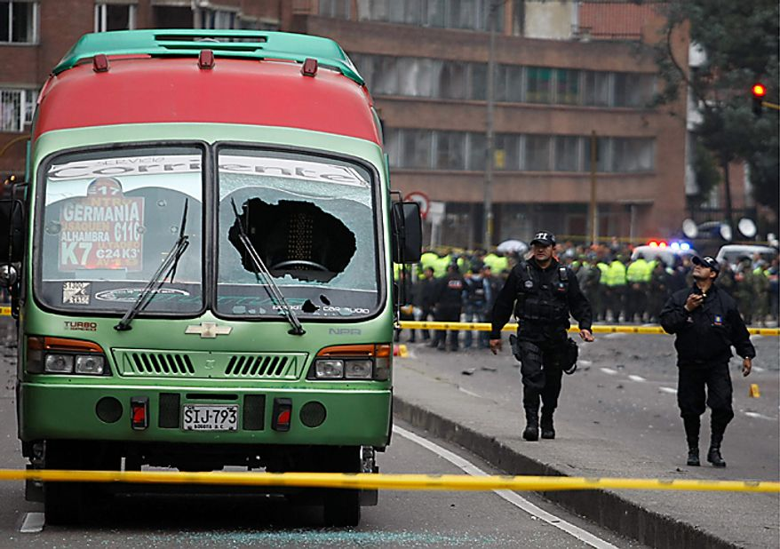 Agents from the police anti explosive unit, walk next to a damaged public bus near the scene of a car bomb explosion, outside the building of Caracol Radio station in Bogota, Colombia, Thursday, Aug. 12, 2010. The explosion shook Colombia's capital on Thursday, injuring at least six people, police said. No deaths were reported. (AP Photo/William Fernando Martinez)