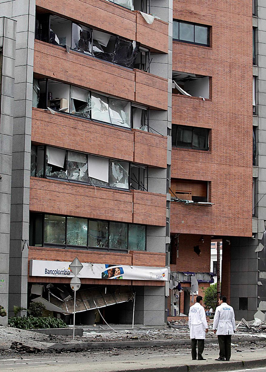 Agents, from the police anti explosive unit, stand at the scene of a car bomb explosion outside the building of Caracol Radio station in Bogota, Colombia, Thursday, Aug. 12, 2010. The car bomb explosion outside a major radio station shook Colombia's capital on Thursday, injuring at least six people, police said. No deaths were reported. (AP Photo/Fernando Vergara)