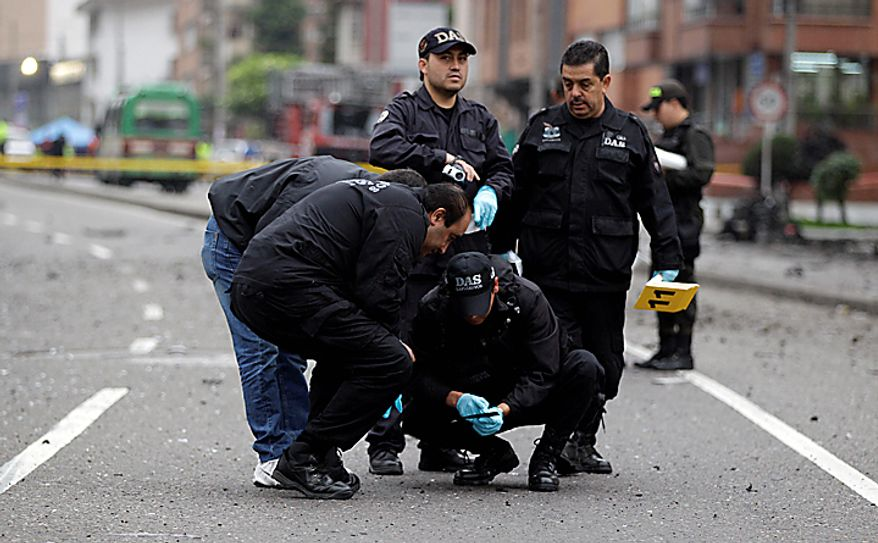 Agents, from the police anti explosive unit, collect evidence at the scene of a car bomb explosion outside the building of Caracol Radio station in Bogota, Colombia, Thursday, Aug. 12, 2010. The car bomb explosion outside a major radio station shook Colombia's capital on Thursday, injuring at least six people, police said. No deaths were reported. (AP Photo/Fernando Vergara)