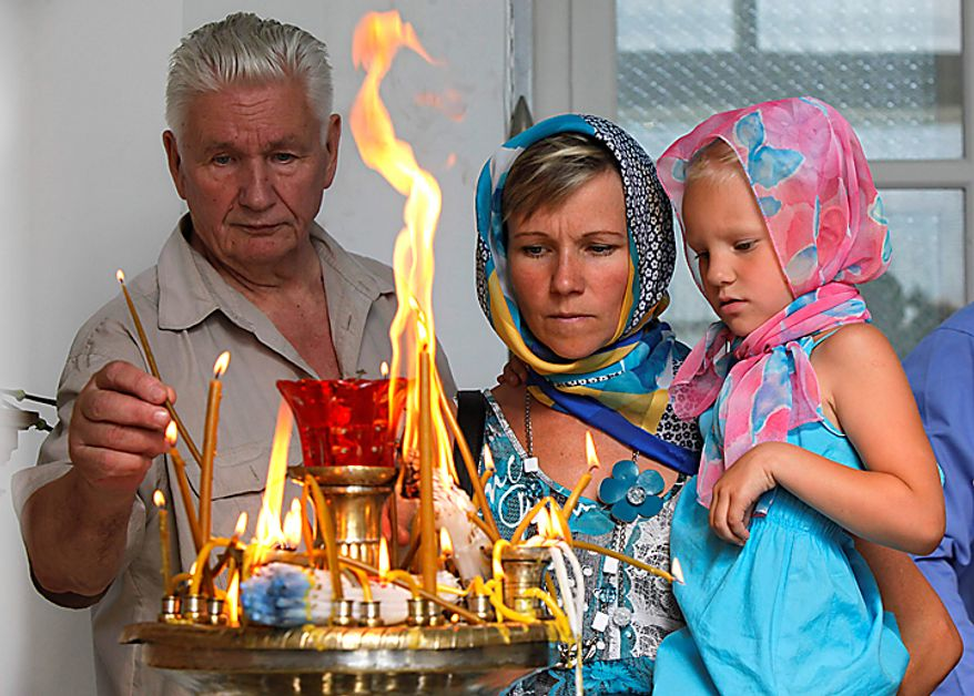 People light candles at St. Nicolas Cathedral, place, where the list of submarine disaster is displayed, in St. Petersburg, Russia, Thursday, Aug. 12, 2010. Russian navy ships are flying flags at half-mast and memorial ceremonies are being held across the nation to commemorate the 10th anniversary of the Kursk nuclear submarine disaster. (AP Photo/Dmitry Lovetsky)