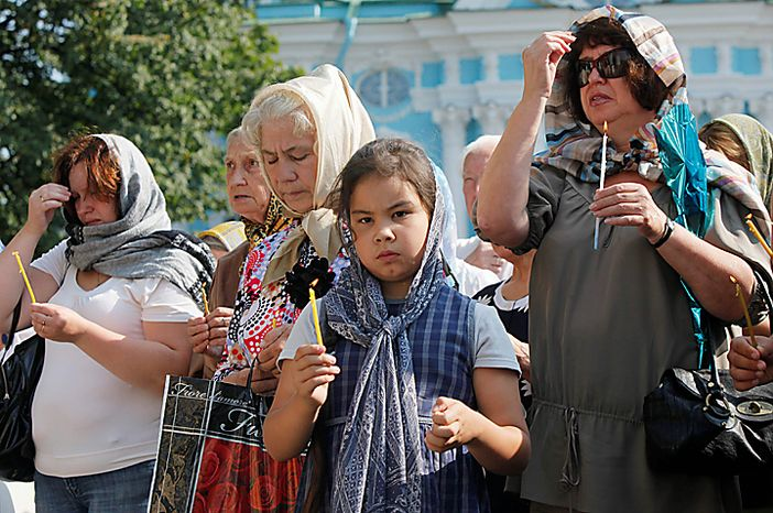 People pray outside the St. Nicolas Cathedral, place, where the list of submarine disaster victims is displayed, in St.Petersburg, Russia, Thursday, Aug. 12, 2010. Russian navy ships are flying flags at half-mast and memorial ceremonies are being held across the nation to commemorate the 10th anniversary of the Kursk nuclear submarine disaster. (AP Photo/Dmitry Lovetsky)