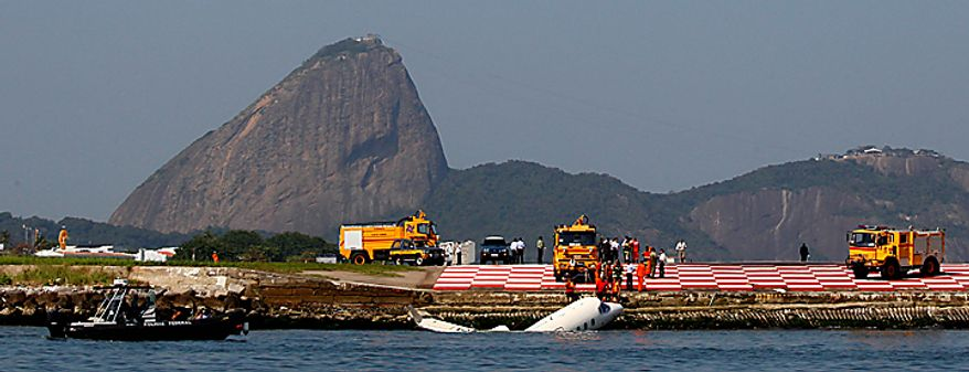 Workers try to pull a small jet from the ocean in Guanabara Bay after it crashed at Rio de Janeiro's domestic airport, Brazil, Thursday, Aug. 12, 2010. All three people aboard survived. The Sugar Loaf mountain stands at back. (AP Photo/Felipe Dana)