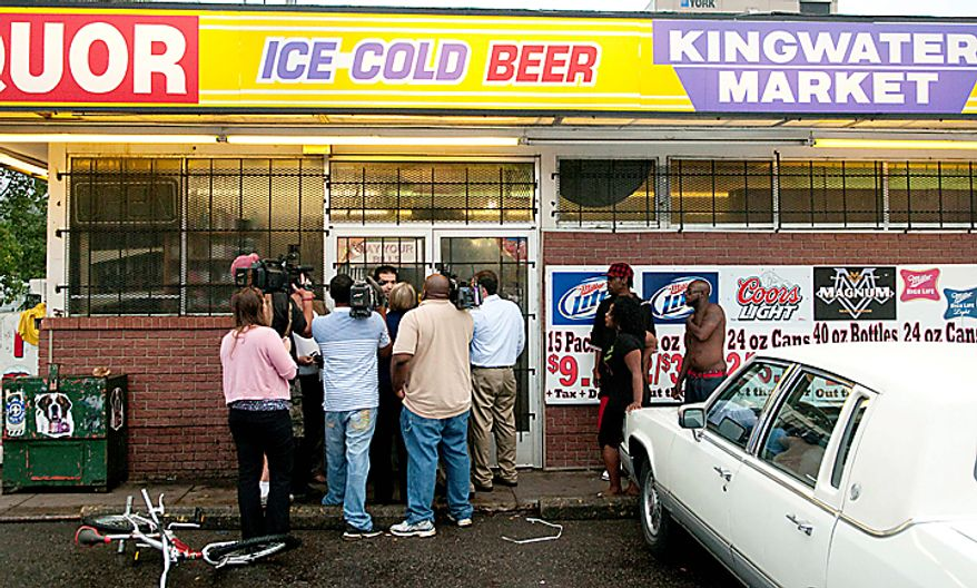 Residents listen as Abdullah Farrah, manager of Kingwater Market in Mount Morris Township, Mich. speaks to members of the media Thursday Aug. 12, 2010. Farrah said police came and reviewed surveillance video as part of an investigation into a multistate stabbing spree concentrated in the Flint area. He said the man who worked at his store and police inquired about drove a vehicle that matched a description and video released by authorities. (AP Photo/The Flint Journal, Ryan Garza)