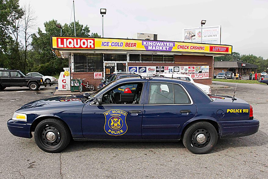 A Mount Morris Township Police car sits outside the Kingwater Market in Mount Morris Township, Flint , Mich., Thursday, Aug. 12, 2010. Abdulla Farrah, the store manager, says police came and reviewed surveillance video as part of an investigation into a multistate stabbing spree concentrated in the Flint, Mich., area. Authorities have arrested a man in Atlanta in connection with a string of stabbings that left five men dead and wounded more than a dozen in Michigan, Virginia and Ohio. Farrah says the man who worked at his store and police inquired about drove a vehicle that matched a description and video released by authorities.  (AP Photo/Paul Sancya)