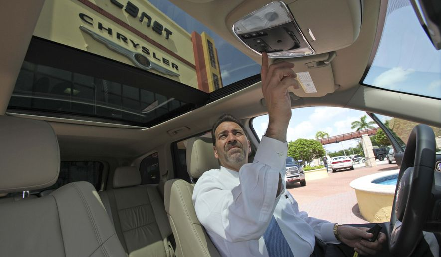 "In this Aug. 11, 2010, photo, Planet Dodge Chrysler Jeep dealership general sales manager Carlos Rodriguez demonstrates how to open the ""CommandView"" panoramic sunroof in a 2011 Jeep Grand Cherokee Limited 4x4 is shown in Doral, Fla. Retail sales managed a modest increase in July after two consecutive declines, but the strength was concentrated in higher sales of autos and gasoline. (AP Photo/Wilfredo Lee)"