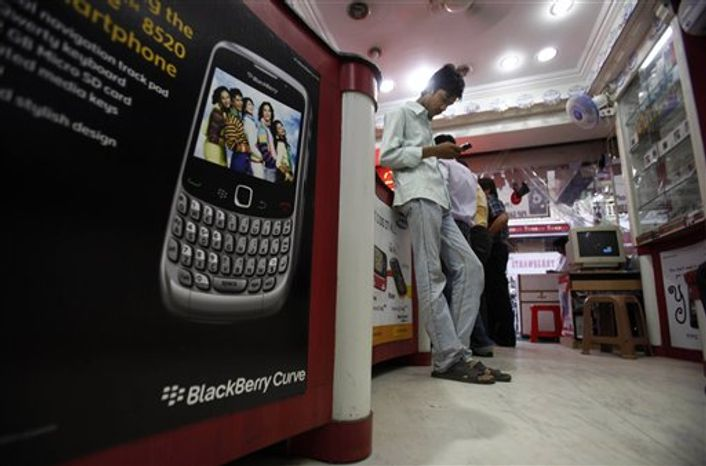 In this photo taken on Friday Aug. 27, 2010,  a shopkeeper displays BlackBerry mobile phones in his shop in Ahmadabad, India.  Indian authorities are scheduled to meet Monday evening, Aug. 30,  to decide whether to ban some BlackBerry services in India, an official said, one day ahead of a government-imposed deadline for BlackBerry maker Research In Motion Ltd. to give security agencies access to encrypted data or face a ban. (AP Photo/Ajit Solanki)