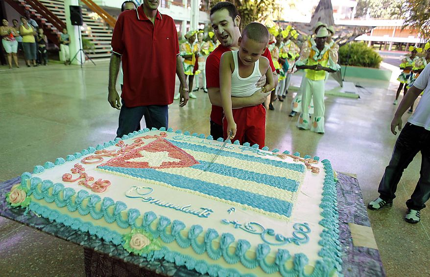 "A boy cuts a cake decorated with a Cuban flag that reads in Spanish ""Congratulations Commander"" at an event honoring Fidel Castro's 84th birthday at the Ernesto ""Che"" Guevara Palace of Pioneers in Havana, Cuba, Friday Aug. 13, 2010. (AP Photo/Javier Galeano)"