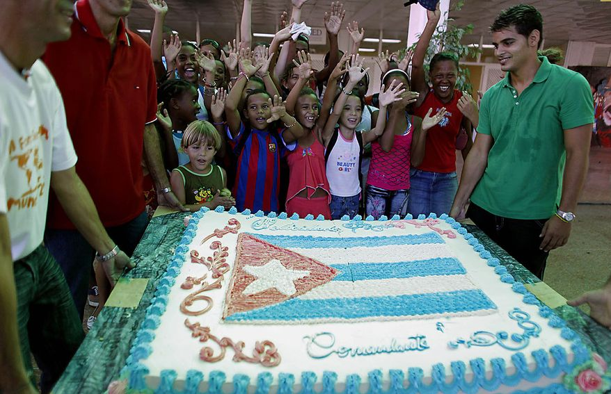 """Children sing a birthday song next to a cake that reads in Spanish """"Congratulations Commander"""" at an event honoring Fidel Castro's 84th birthday at the Ernesto """"Che"""" Guevara Palace of Pioneers in Havana, Cuba, Friday Aug. 13, 2010. (AP Photo/Javier Galeano)"""