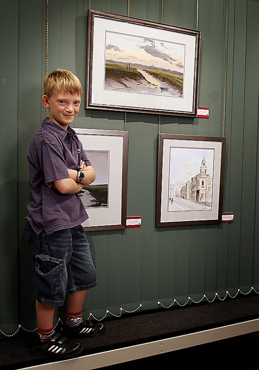 In this Thursday, Aug. 12, 2010 Kieron Williamson, an eight-year-old painting prodigy stands by some of his work displayed in an art gallery in Holt, Norfolk in England. He's Britain's most talked-about young artist. His paintings sell for thousands of dollars and there's a long waiting list for his eagerly anticipated new works. (AP Photo/Kirsty Wigglesworth)