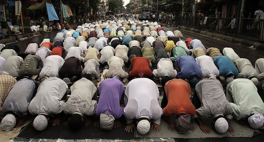 Muslims pray on the roadside in Calcutta, India, Friday, Aug. 13, 2010. Muslims throughout the world are marking the month of Ramadan, the holiest month in Islamic calendar where observant fast from dawn till dusk. (AP Photo/Bikas Das)