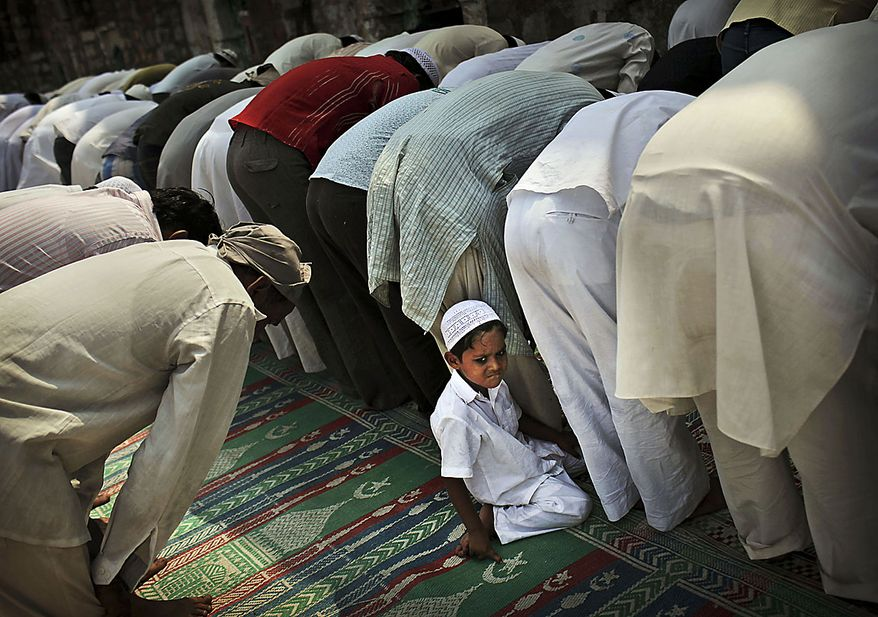 An Indian Muslim boy takes shade behind men offering Friday prayers at the Feroz Shah Kotla Mosque in New Delhi, India, Friday, Aug. 13, 2010. Muslims throughout the world are marking the month of Ramadan, the holiest month in the Islamic calendar where the observant fast from dawn till dusk. (AP Photo/Kevin Frayer)