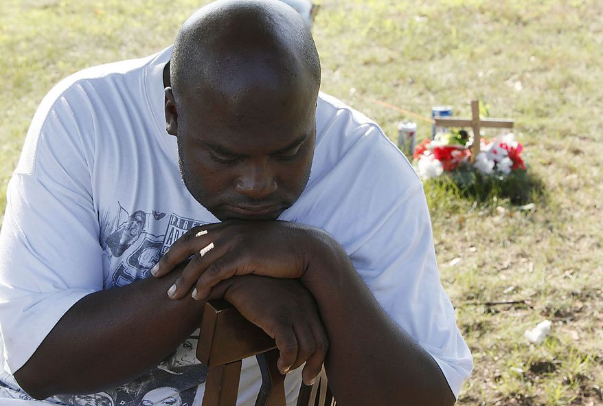 Anthony Cheathams Sr., mourns at the site where David Motley was killed in Flint, Mich., Thursday, Aug. 12, 2010. Elias Abuelazam, the suspect in a string of stabbings that terrorized people across three states and left five dead, was charged Thursday with assault with intent to murder in connection with a July 27 stabbing in Flint. Abuelazam was arrested at a gate at Hartsfield-Jackson Atlanta International Airport as he tried to board a plane for Israel, officials said Thursday. (AP Photo/Paul Sancya)