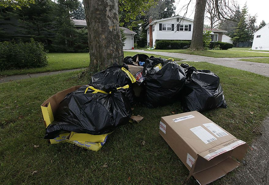 Garbage authorities searched sits outside a home in Flint , Mich., Thursday, Aug. 12, 2010. The box shown was shipped to Elias Ebuelazam. A suspect in a string of 20 stabbings that terrorized people across three states and left five dead was arrested in front of startled passengers at an airport gate in Atlanta as he tried to board a plane for Israel, officials said Thursday. A judge in Flint, Mich.,  signed a warrant Thursday charging Elias Abuelazam, 33, with assault with intent to murder in connection with a July 27 stabbing. (AP Photo/Paul Sancya)