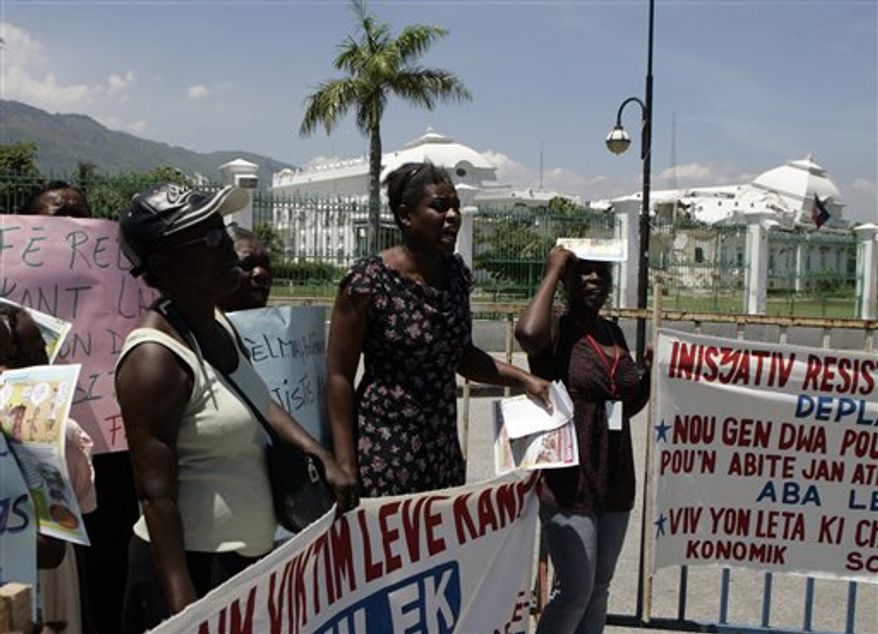 Residents of camps set up for people left homeless by the Jan. 12 earthquake demonstrate in front of  the collapsed presidential palace in Port-au-Prince, Haiti, Thursday, Aug 12, 2010. Demonstrators said the government is failing on its promises to provide housing as private landowners pressure the camp residents to leave. (AP Photo/Dieu Nalio Chery)