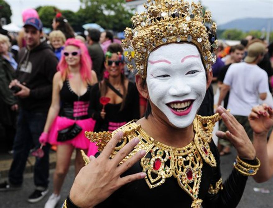Fancy dressed participants of the annual Street Parade celebrate and dance in the city center of Zurich, Switzerland, on Saturday, Aug. 14, 2010. Hundreds of thousands of ravers participate in the event. (AP Photo/Keystone, Steffen Schmidt)
