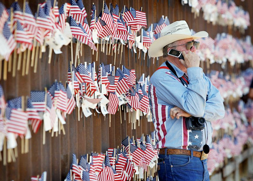 David Walker, an Arizona rancher, stands at a wall on the border with Mexico at a ranch in Hereford, Ariz., on Sunday. Mr. Walker was attending a rally in support of Arizona's immigration law. (Associated Press)