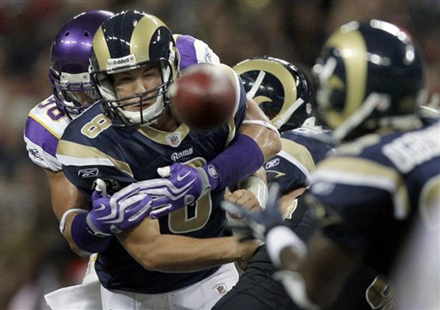 St. Louis Rams quarterback Sam Bradford throws a pass to Rams running back Chris Ogbonnaya, right, while being hit by Minnesota Vikings defensive tackle Letroy Guion, left, during the second quarter of a preseason NFL football game Saturday, Aug. 14, 2010, in St Louis. (AP Photo/Jeff Roberson)