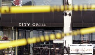 Yellow crime-scene tape stretches across windows that were broken in a train terminal across the street from the scene of a fatal multiple shooting outside the City Grill bar and restaurant in Buffalo, N.Y., on Saturday, Aug. 14, 2010. (AP Photo/David Duprey)
