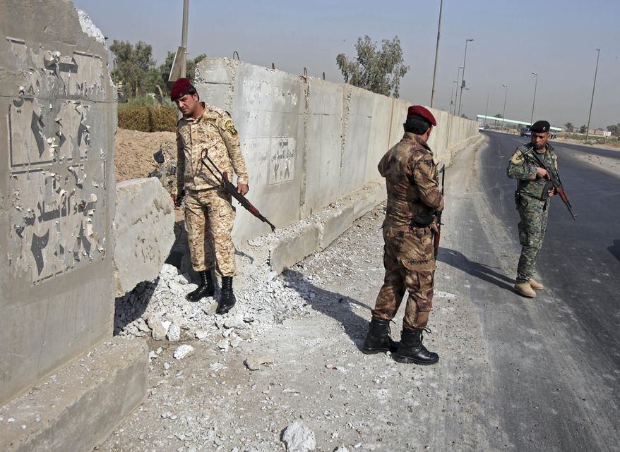 Iraqi army soldiers secure the scene of a roadside bomb attack in Baghdad on Sunday, Aug. 15, 2010. A series of rush-hour bombings across Baghdad has killed and injured scores of people, officials said. (AP Photo/Karim Kadim)