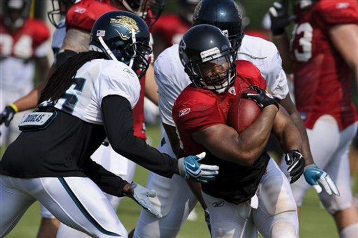 Atlanta Falcons running back Michael Turner (33) carries the ball against the Jacksonville Jaguars during NFL football training camp in Flowery Branch, Ga., Tuesday, Aug. 10, 2010. The Jaguars are in town to scrimmage the Falcons. (AP Photo/Paul Abell)
