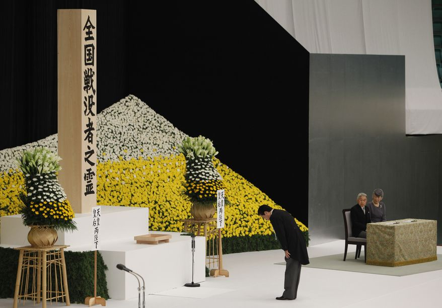 Japanese Prime Minister Naoto Kan bows deeply in front of a huge bank of chrysanthemums to offer prayers for the war dead at Budokan martial arts hall in Tokyo on Sunday, Aug. 15, 2010, in ceremonies marking the 65th anniversary of the end of World War II. (AP Photo/Shizuo Kambayashi)
