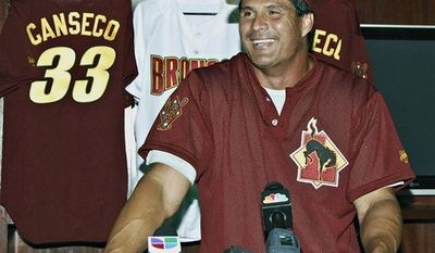 Laredo Broncos' President/General Manager Jose Melendez, left, hands former Major League Baseball slugger Jose Canseco, his new team jersey at a news conference announcing Canseco's signing in Laredo, Texas, Monday aug. 16, 2010. The independent minor league team said that Canseco will serve as bench coach and designated hitter during two Broncos' homestands starting Monday. The former American League MVP who admitted to using steroids and alleged that several other players did too, formerly played with two teams in the independent Golden League in 2006. (AP Photo/Laredo MorningTimes, Ulysses S. Romero)