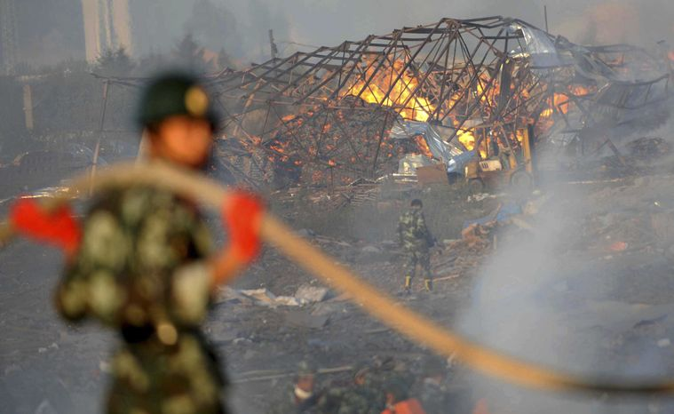 Soldiers take part in firefighting operations at a fireworks factory in the city of Yichun in northeast China's Heilongjiang province on Monday, Aug. 16, 2010. A massive explosion ripped through the factory, killing 13 workers, damaging nearby buildings and causing secondary blasts. (AP Photo/Xinhua News Agency, Wang Jianwei)