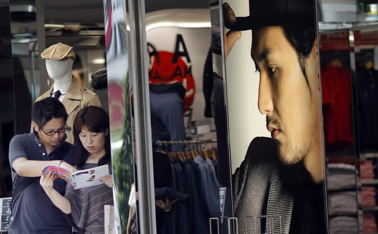 Tourists stop at a clothing shop in Tokyo Monday, Aug. 16, 2010. Japan lost its place as the world's No. 2 economy to China in the second quarter as receding global growth sapped momentum and stunted a shaky recovery. (AP Photo/Junji Kurokawa)