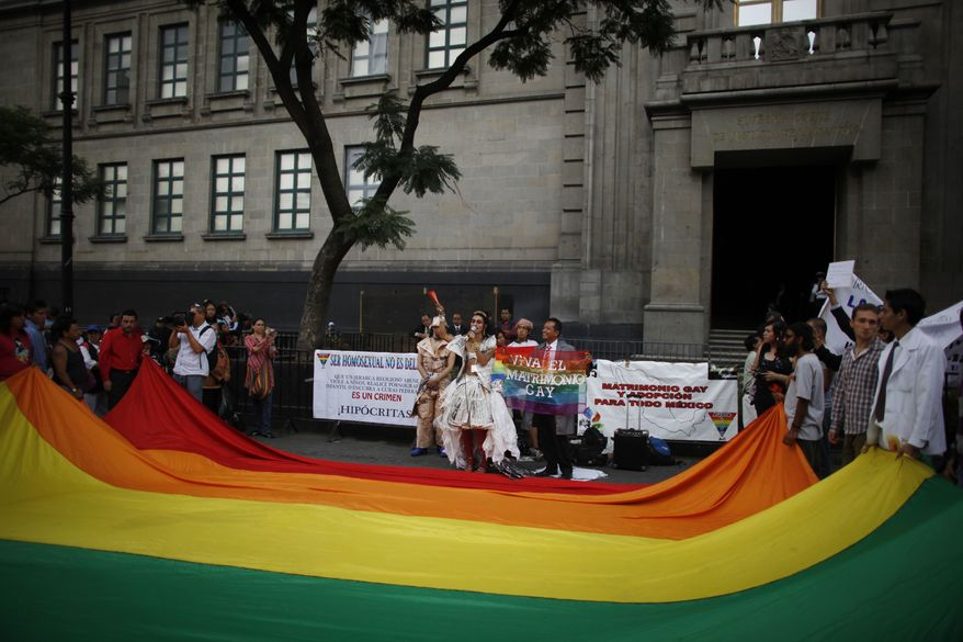** FILE ** Gay rights activists demonstrate in favor of the legality of adoptions by gay couples outside the Supreme Court in Mexico City on Thursday, Aug. 12, 2010. The high court on Monday upheld a Mexico City law allowing the adoptions. (AP Photo/Alexandre Meneghini)