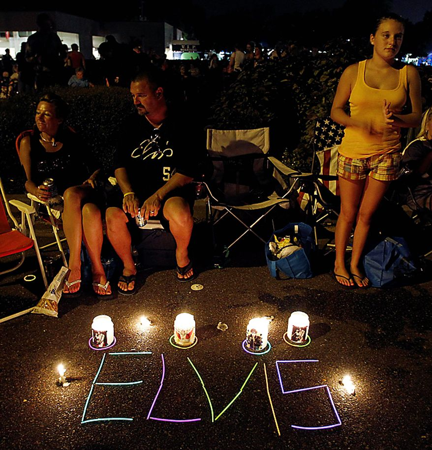 Dawn Wahligh, left, her husband, John, center, and their niece, Jaycie, 13, right, sit on Elvis Presley Boulevard outside Graceland, Presley's Memphis, Tenn., home, on Sunday, Aug. 15, 2010. They were waiting to get in the line to walk to Presley's grave. Presley fans from around the world are at Graceland for the annual nighttime procession past his grave on the eve of his death. Presley died at the home Aug. 16, 1977. (AP Photo/Mark Humphrey)