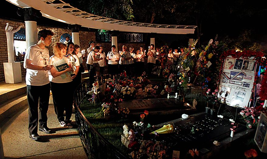 Elvis Presley fans hold candles as they visit Presley's grave at Graceland, his Memphis, Tenn., home, on Sunday, Aug. 15, 2010. Presley fans from around the world are at Graceland for the annual nighttime procession past his grave on the eve of his death. Presley died at the home Aug. 16, 1977. (AP Photo/Mark Humphrey)
