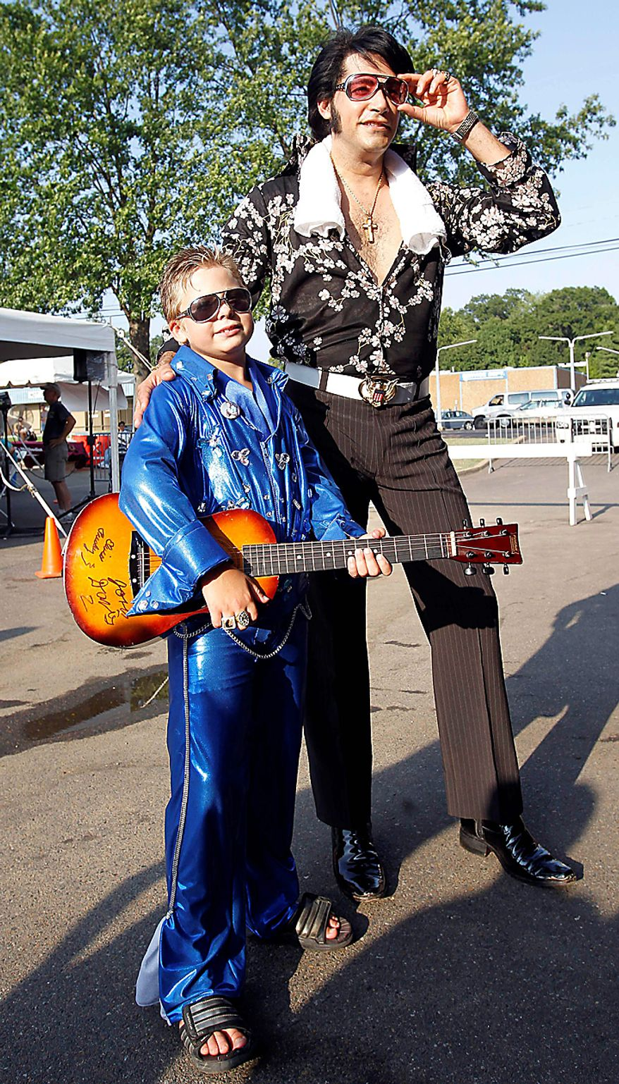 Elvis Presley impersonator Mark Rio, right, of Brazil, poses for a photo with Brandon Bird, 8, of Manhattan, Ill., on Sunday, Aug. 15, 2010 in Memphis, Tenn. Presley fans from around the world are at Graceland, Presley's Memphis home, for the annual nighttime procession past his grave on the eve of his death. Presley died at the home Aug. 16, 1977.  (AP Photo/Mark Humphrey)