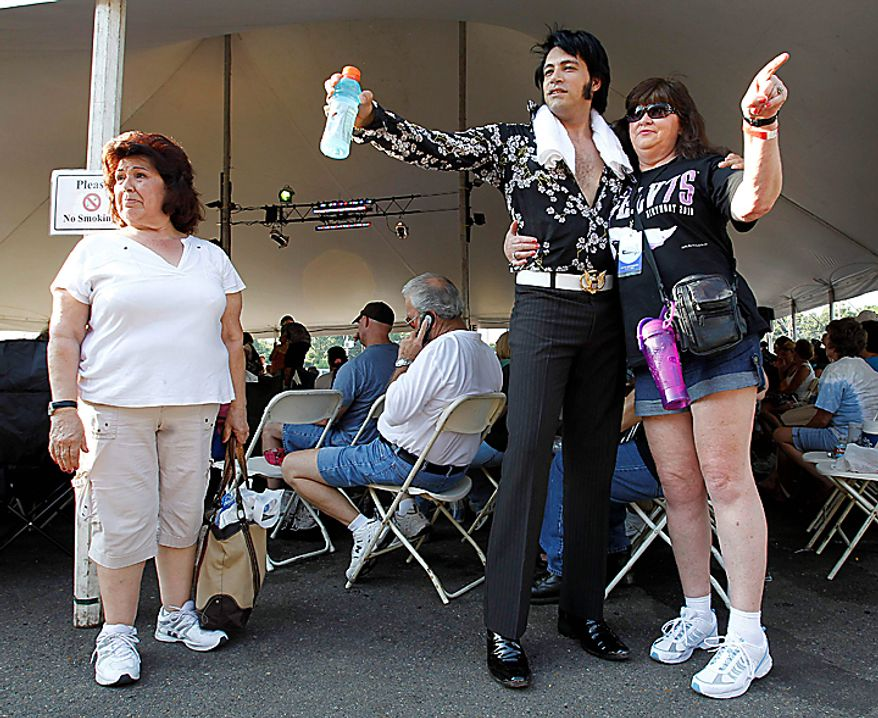 Pat Parker, right, of Leeds, Ala., tells Elvis Presley impersonator Mark Rio, center, of Brazil, which way to look for a souvenir photo on Sunday, Aug. 15, 2010, in Memphis, Tenn. Waiting her turn to get her photo made with Rio is Carol Kelley, left, of Santa Rosa, Ca.  Presley fans from around the world are at Graceland for the annual nighttime procession past his grave on the eve of his death. Presley died at the home Aug. 16, 1977. (AP Photo/Mark Humphrey)